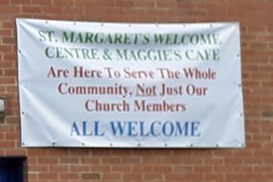 Banner on outside wall reads: St Margaret's Welcome Centre and Maggie's Cafe are here to serve the whole community NOT just our church members - ALL WELCOME