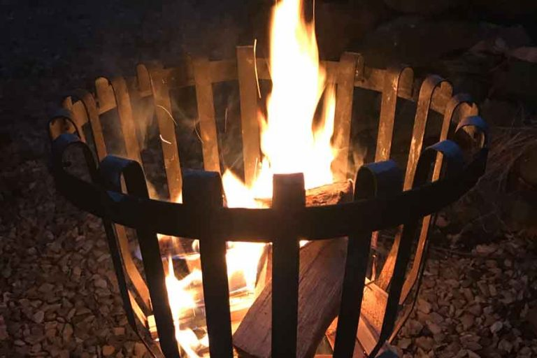 Flames shoot up from a brazier in the dark