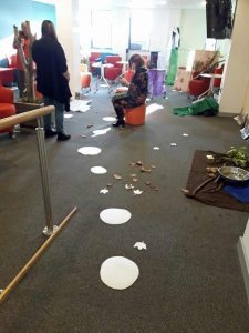 Paper stepping stones and leaves lead into a room themed as a wood