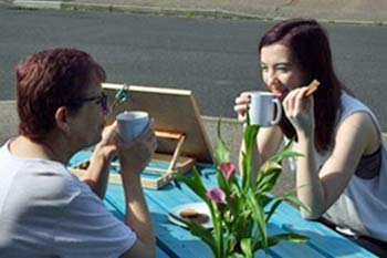 Two women have coffee and biscuits sat opposite each other on a turquoise picnic table by the roadside