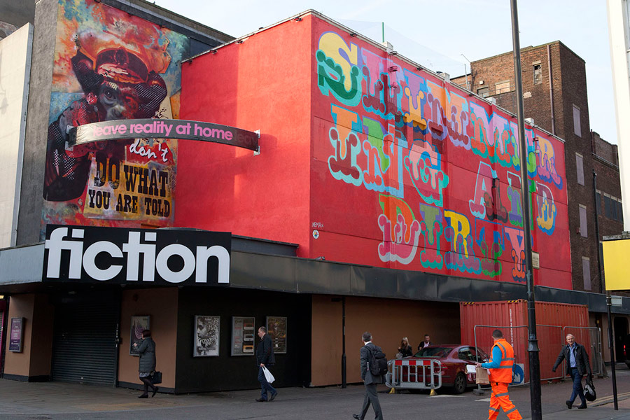"colourful large scale lettering on a bright red hoarding in Romford, spelling out ""shimmering and dirty"""