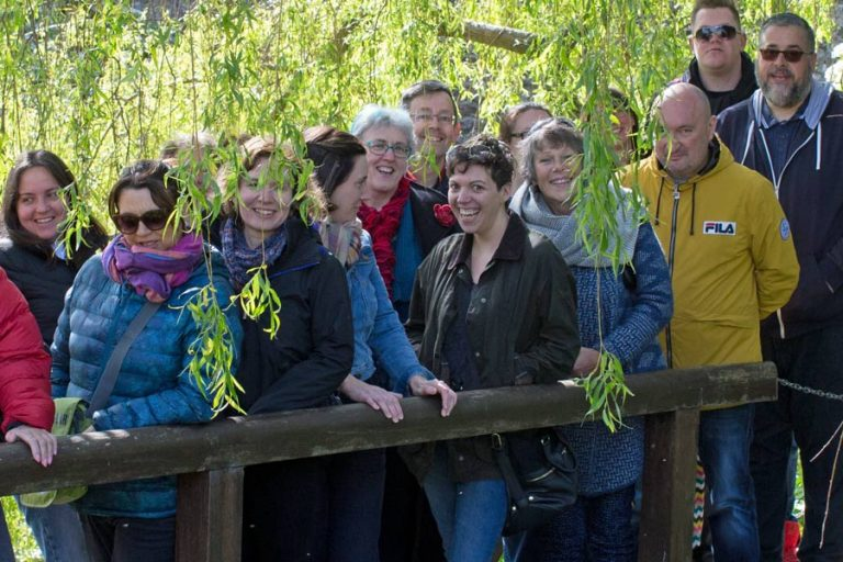 Group of smiling people on footbridge among greenery