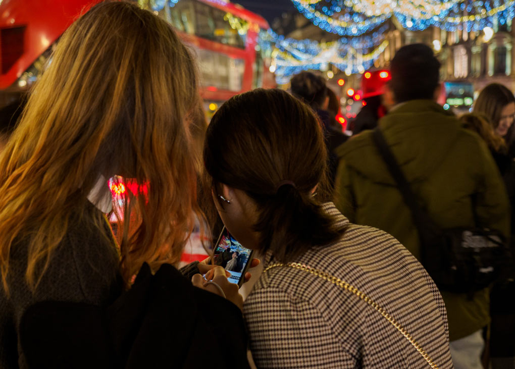 Two young women seen from behind looking at phone amid bright central London lights