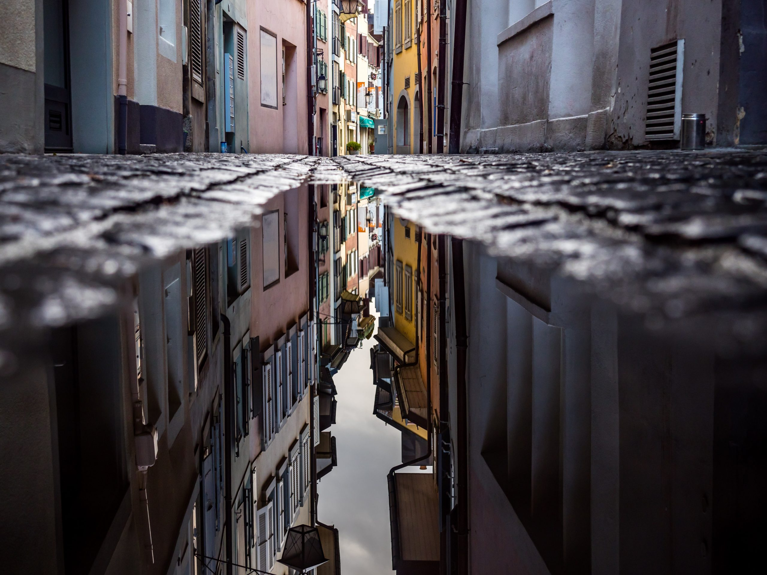 Narrow lanes in mediterranean city reflected in large puddle