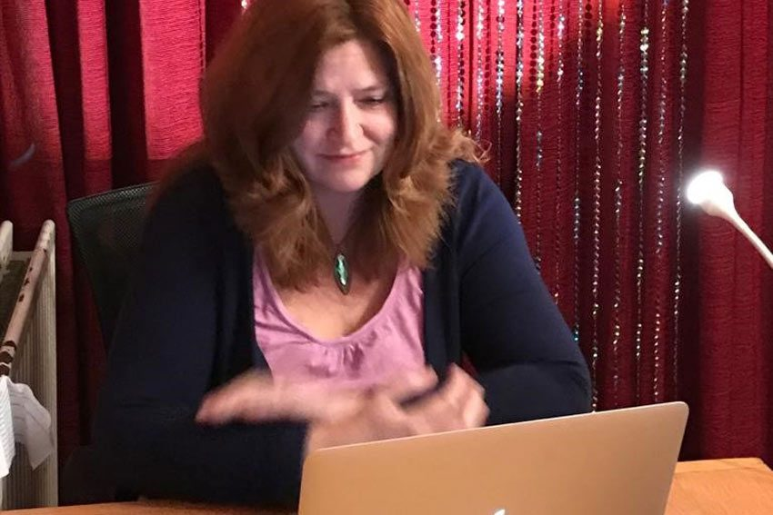 Andrea campanale seated behind a laptop with red curtain backdrop