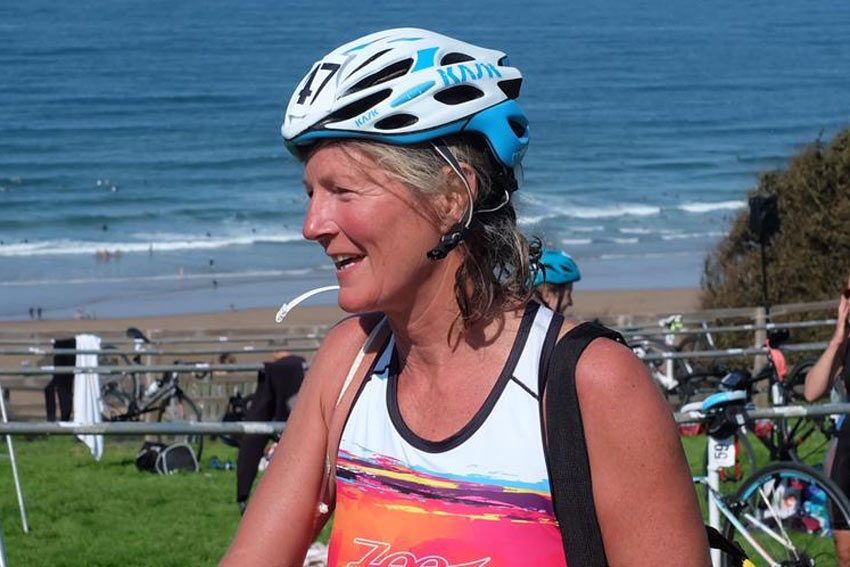 Sun tanned woman in cycling helmet by the sea