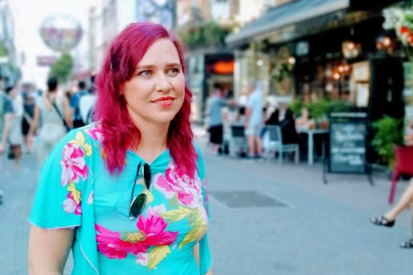 Woman with deep pink hair and turquoise t-shirt stands in a paved high street