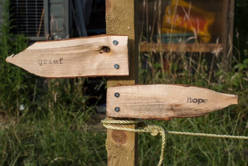 wooden signpost facing in two directions: