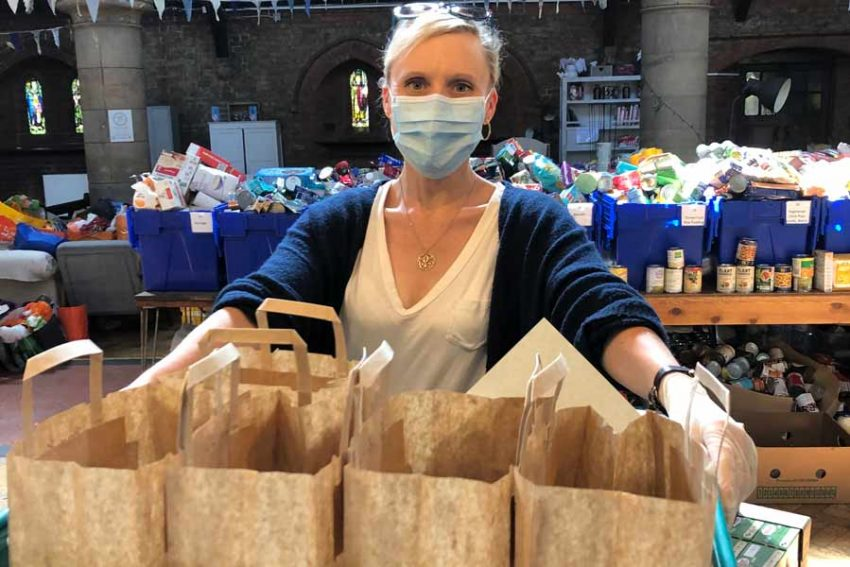 woman with tray of brown paper bags, food crates in backgournd