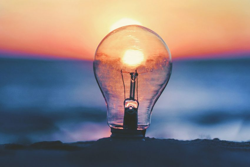 light bulb with setting sun behind, forming the filament