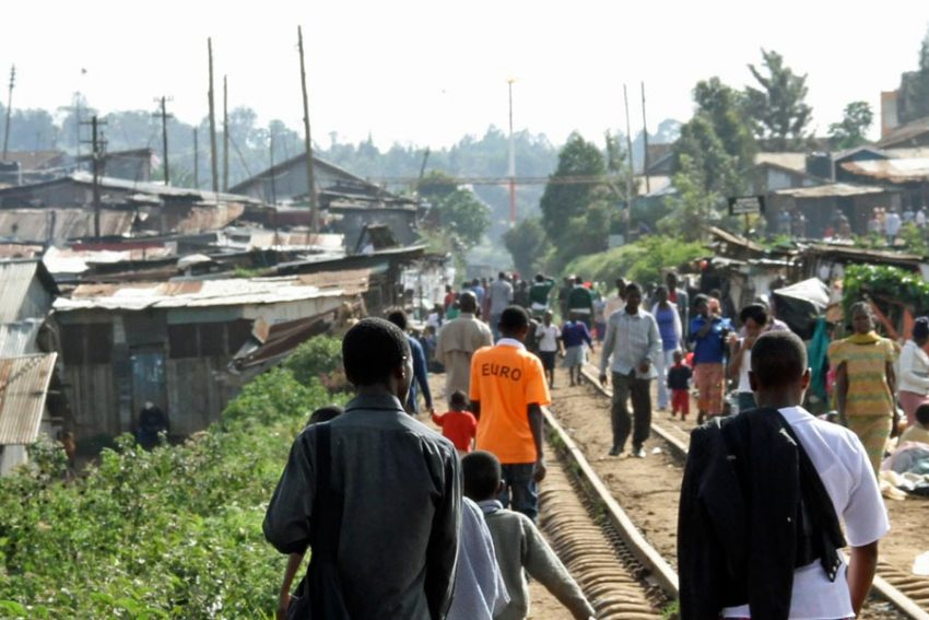 People walking along a rail track in Kibera, Nairobi, Kenya